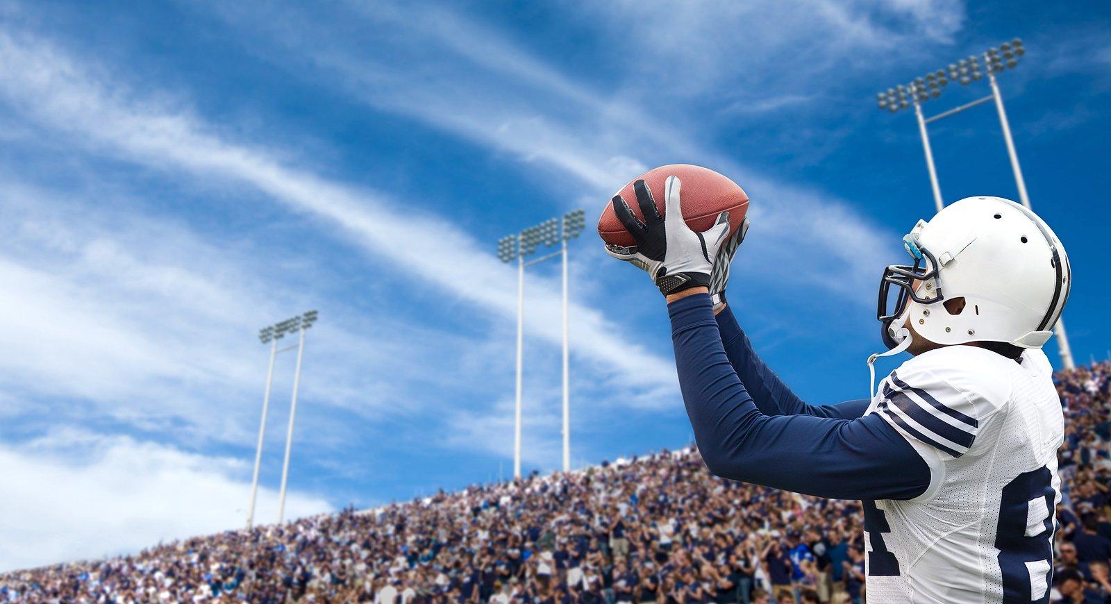 bigstock-Football-Player-catching-a-tou-22198955
